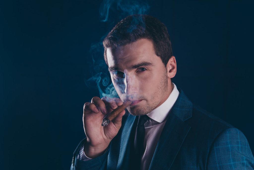 A smartly dressed man enjoys a lit cigar.