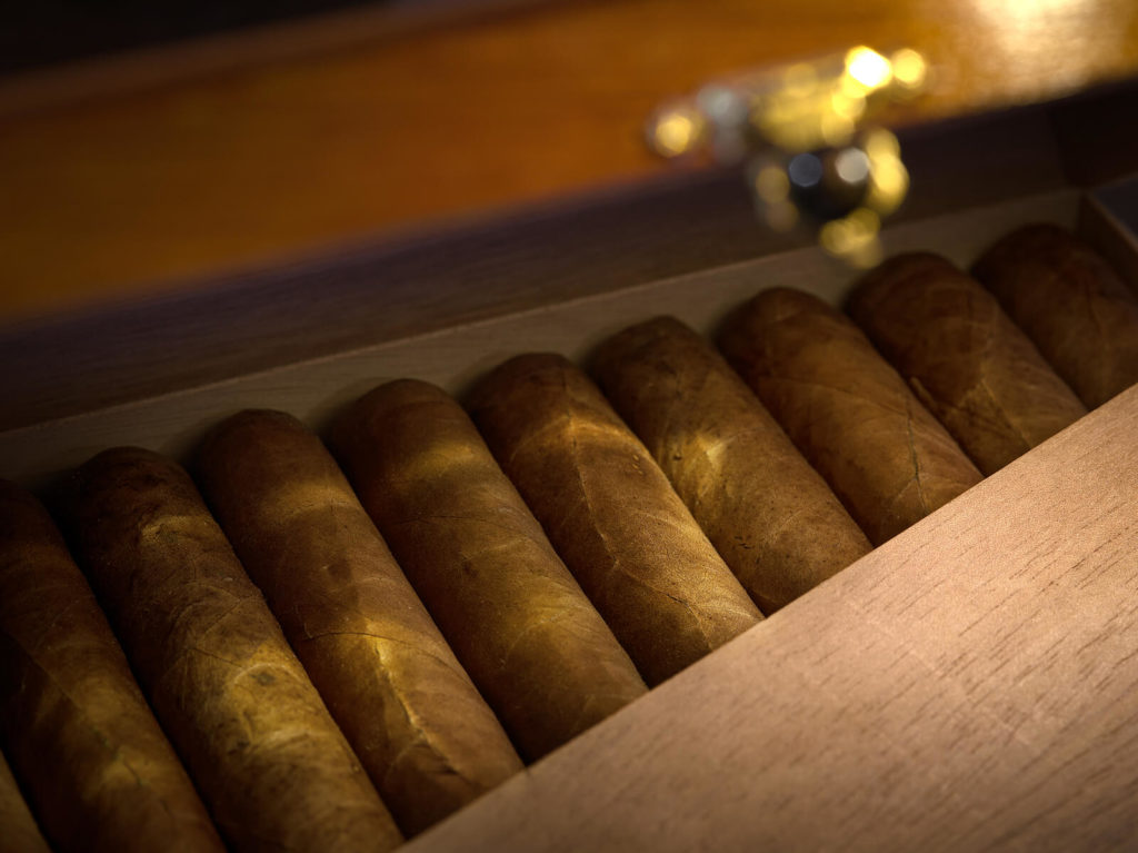 A humidor sits filled to the brim with high-quality cigars.