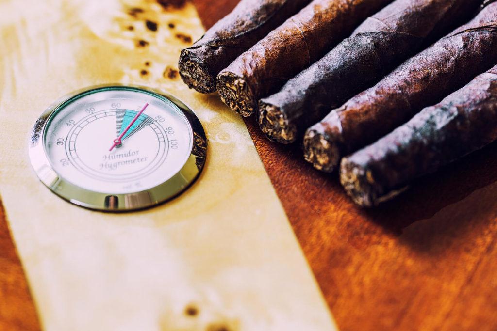 Fresh cigars sit next to a hygrometer.