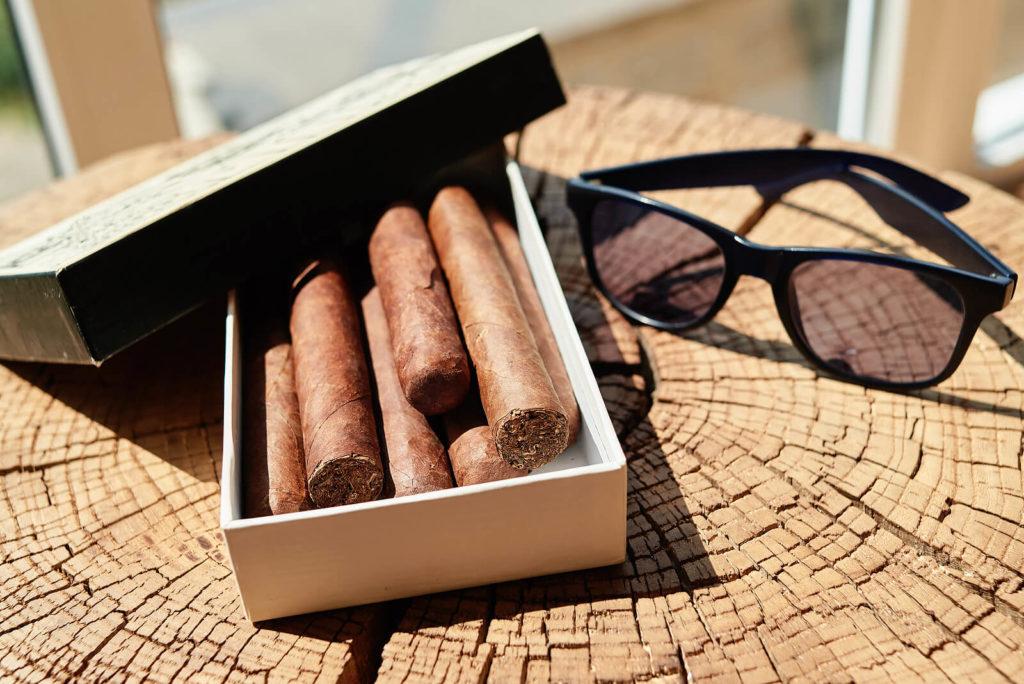 Cigars sat in the sun, stored in a cardboard box.