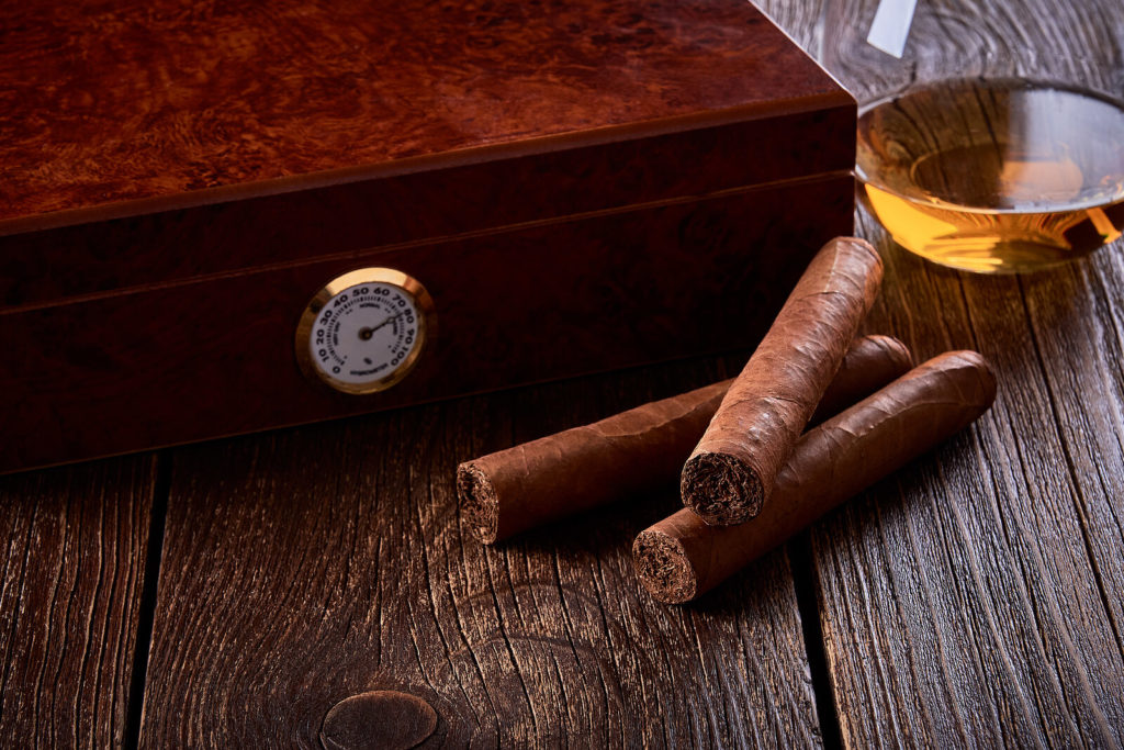 Two cigars sit outside a stylish humidor with a glass of whiskey.